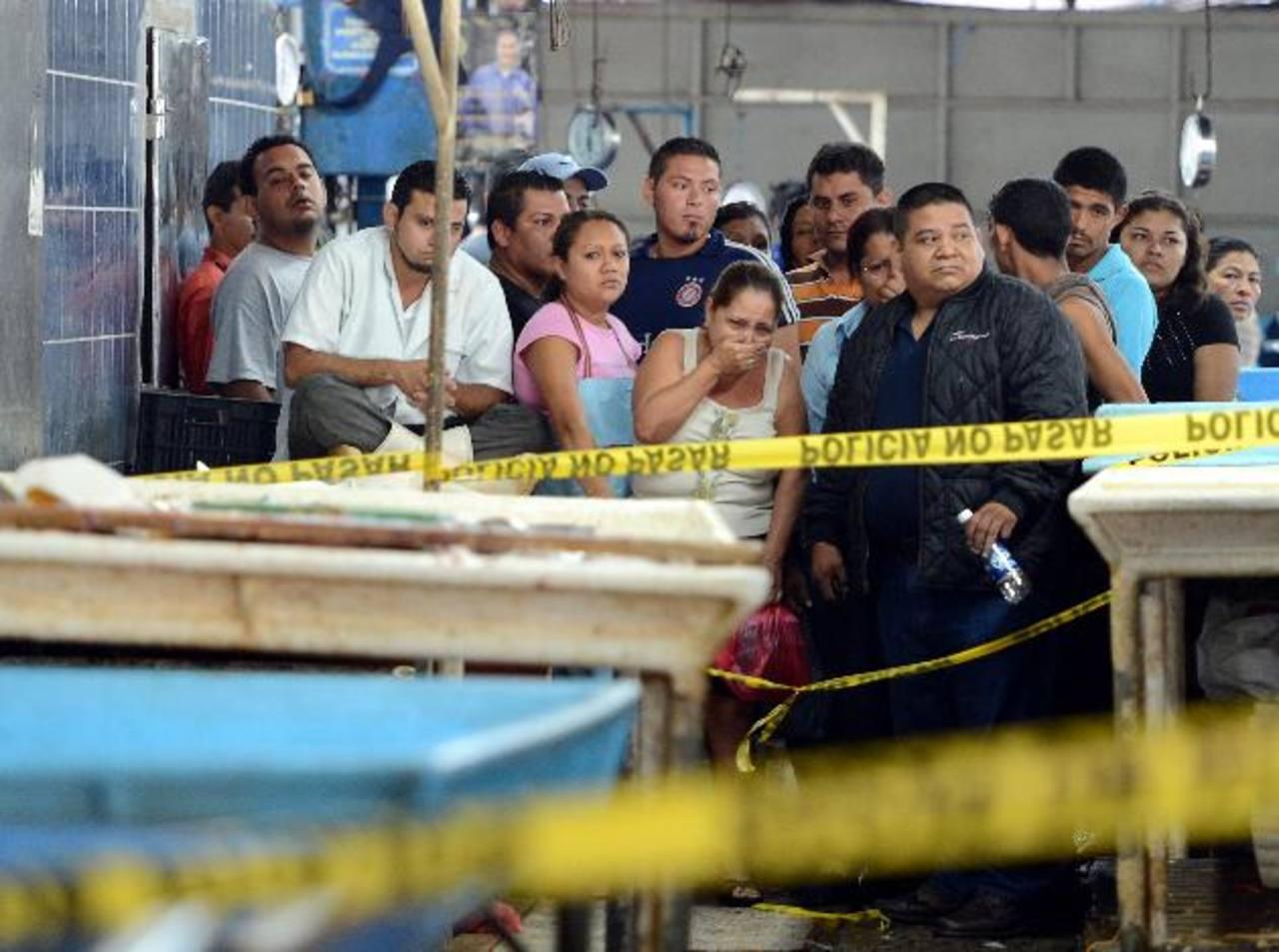 Curiosos observan el sitio donde ayer asesinaron a José Adalberto Espinoza García en el puesto en el que vendía mariscos en el mercado La Tiendona. Las primeras investigaciones apuntan a supuestos problemas con otros comerciantes. Foto EDH / Archivo