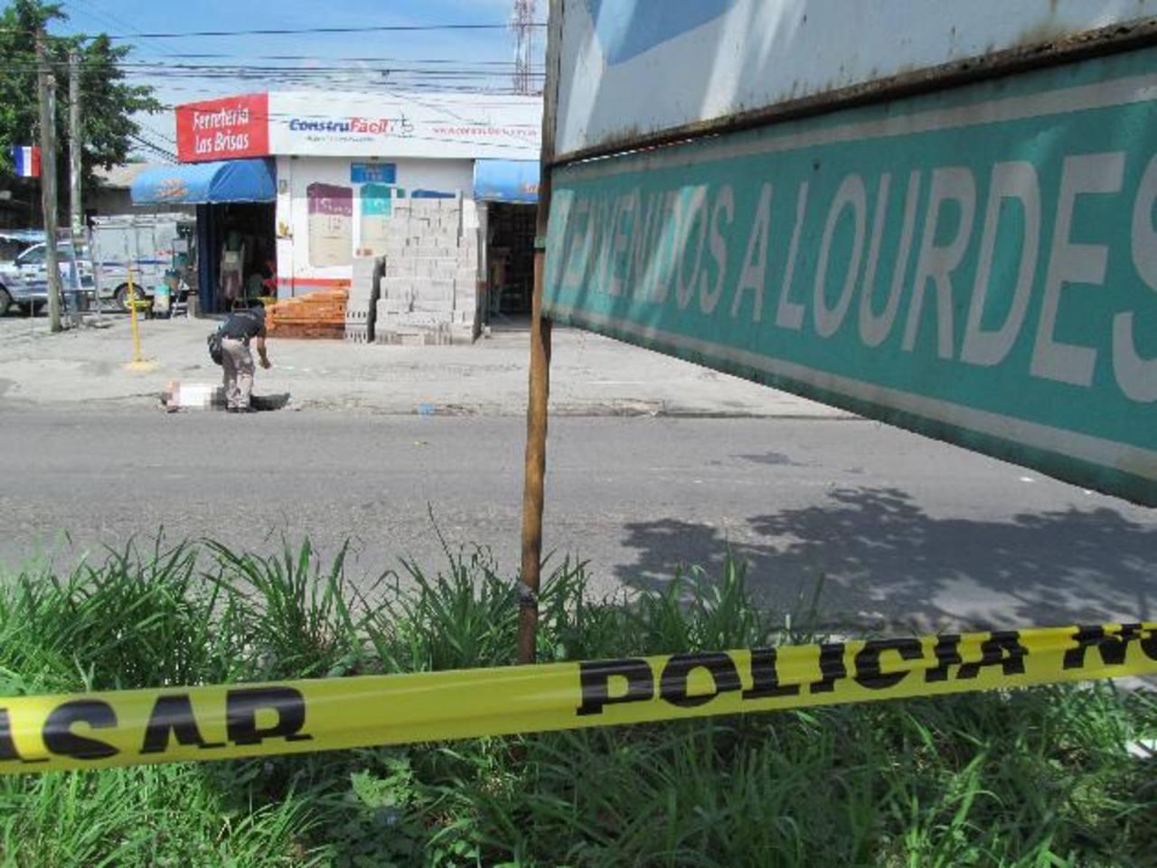 Un policía inspecciona el cuerpo de un hombre asesinado por tres pandilleros que, en su huida, se enfrentaron a investigadores policiales quienes balearon a un sospechoso. Foto EDH