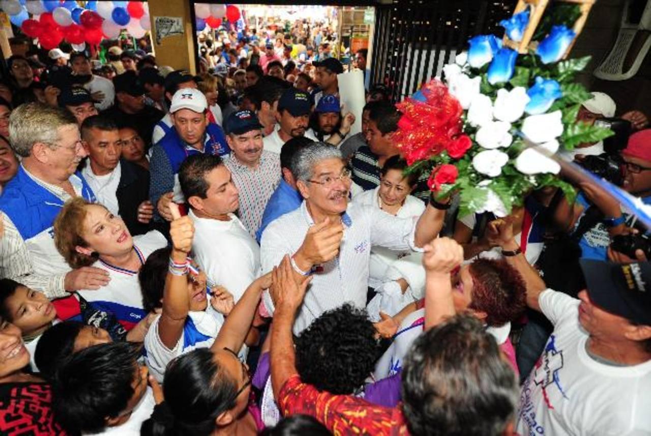 Quijano recibe un arreglo floral por parte de vendedoras durante una visita al Mercado Central. foto edh / lissette lemus
