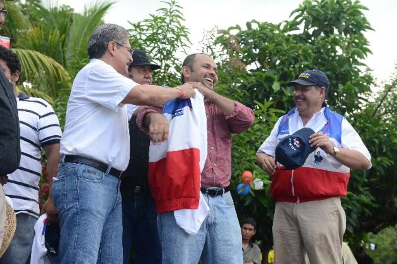 Norman Quijano pone el chaleco tricolor a Alexander Calles, exdirector departamental de Gana en Usulután, para oficializar su adhesión a ARENA. fotos edh / miguel villalta