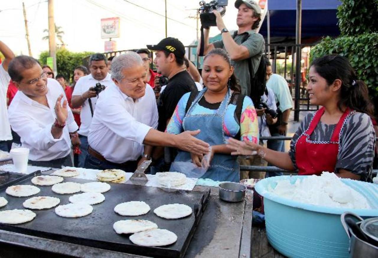 Salvador Sánchez Cerén y Óscar Ortiz saludan a unas vendedoras frente a la UES, donde culminaron su caminata. Foto EDH