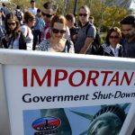 Numerosas personas leen un cartel que anuncia que la Estatua de la Libertad permanece cerrada, debido al cierre parcial del Gobierno estadounidense, en Nueva York. Lo mismo ocurrió en otros sitios emblemáticos. foto EDH /EFE