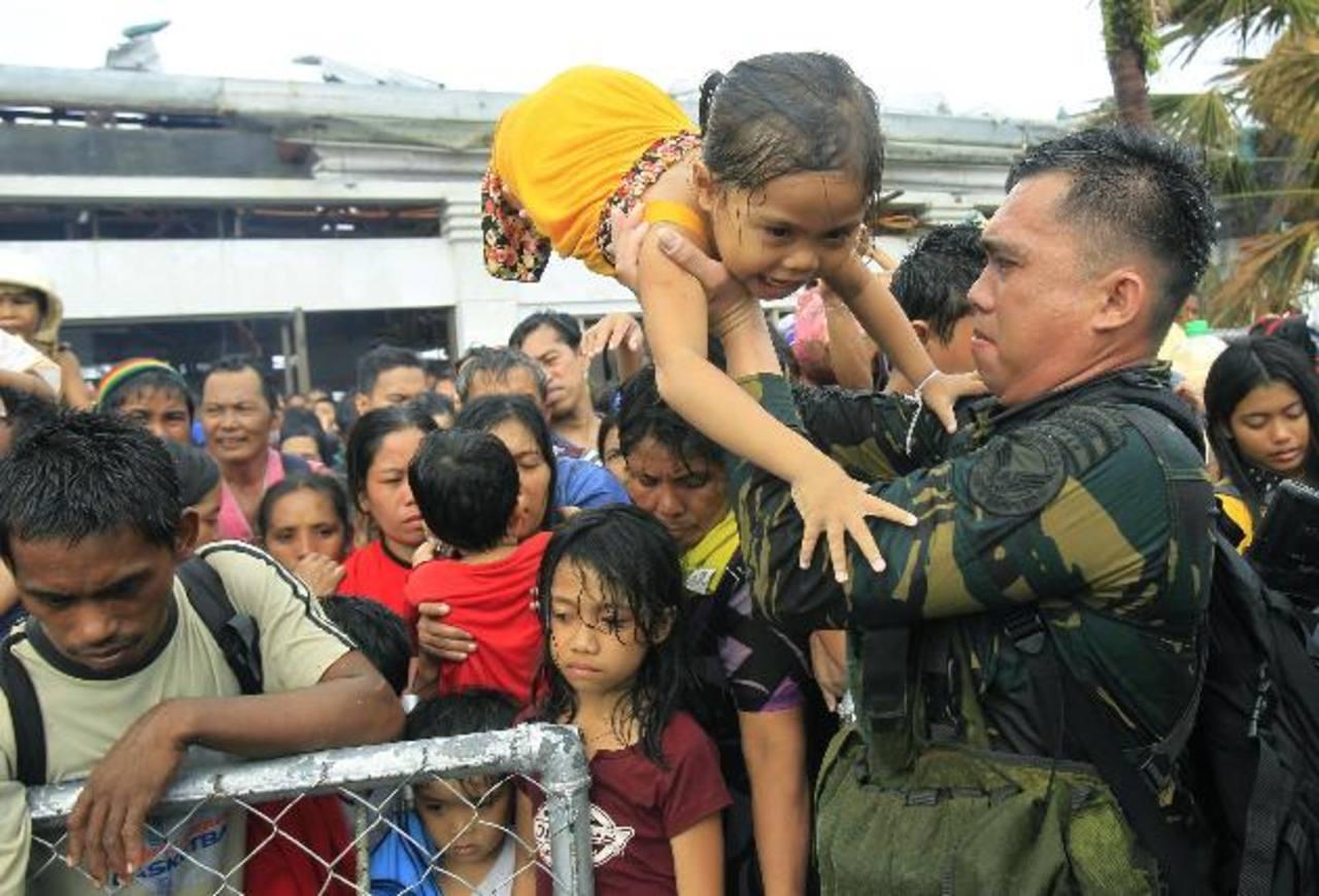 Militar filipino trata de dar prioridad a los niños y las mujeres entre miles de personas que esperaban ser evacuadas por avión en Tacloban. Foto/ AP