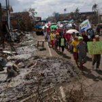 """En Filipinas, caminantes cantaban la canción """"Venceremos"""" para levantar los ánimos de todos los sobrevivientes del tifón Haiyán. FOTO AP"""