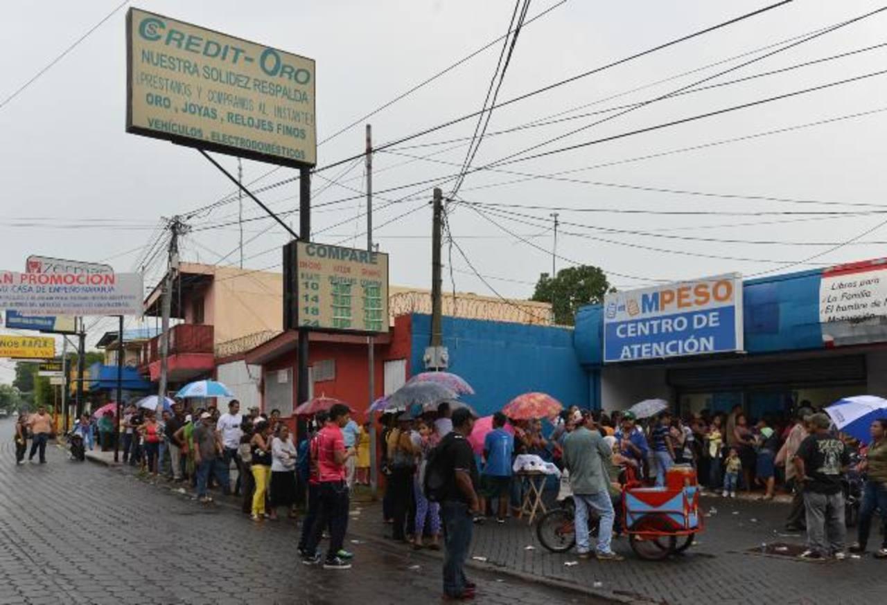 Nicaragüenses tuvieron que hacer largas filas frente a oficinas de Mpeso para obtener la tarjeta de buses. EDH/Iván Olivares.