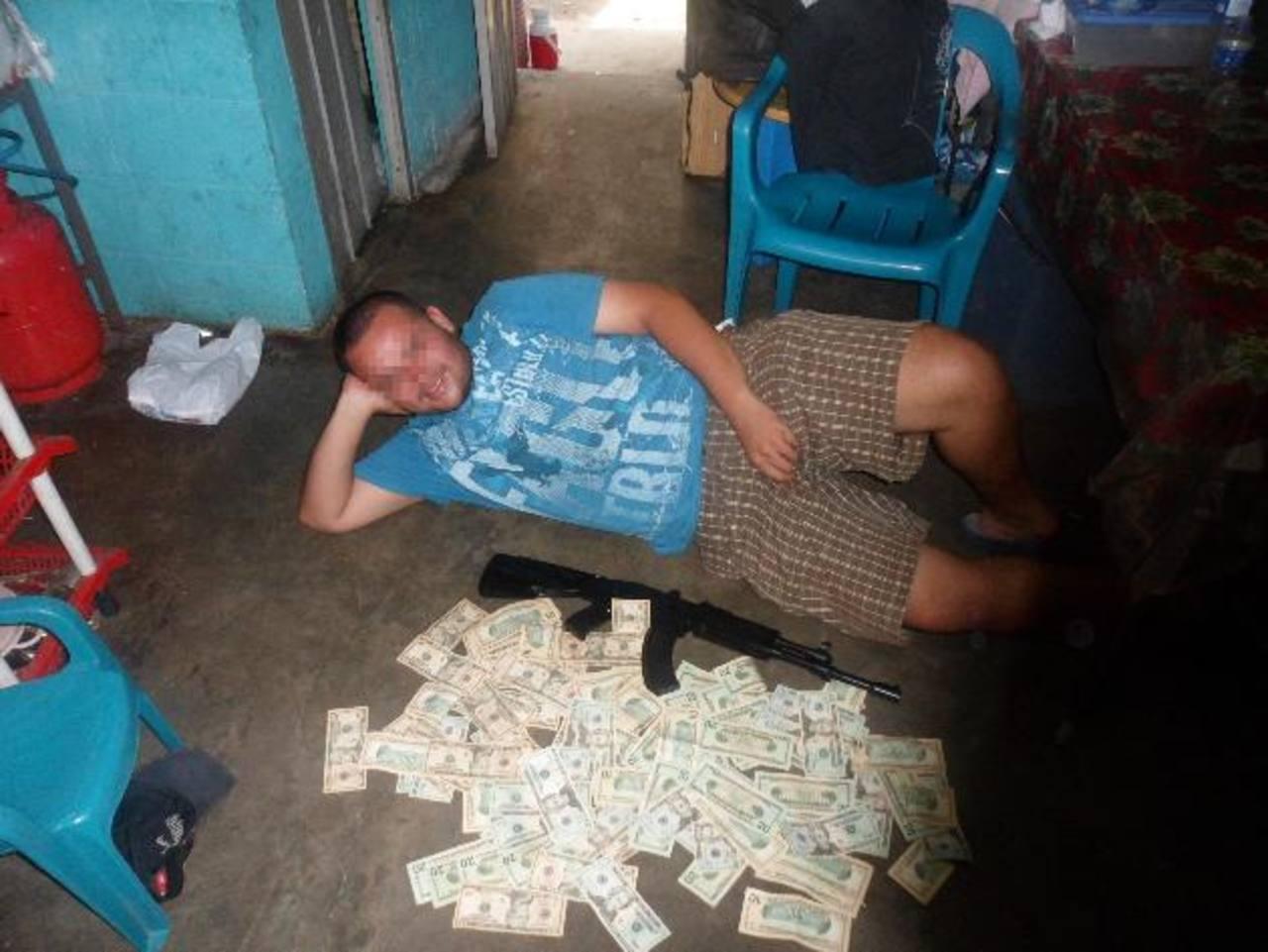 Pandillero del Barrio 18, del barrio San Miguelito, posa frente a un cúmulo de billetes, producto de las extorsiones. Foto EDH