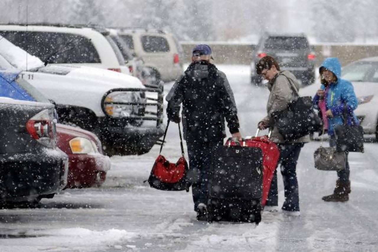 Viajeros tratan de llegar a su coche después de salir del Aeropuerto Internacional de Pittsburgh. foto edh / ap