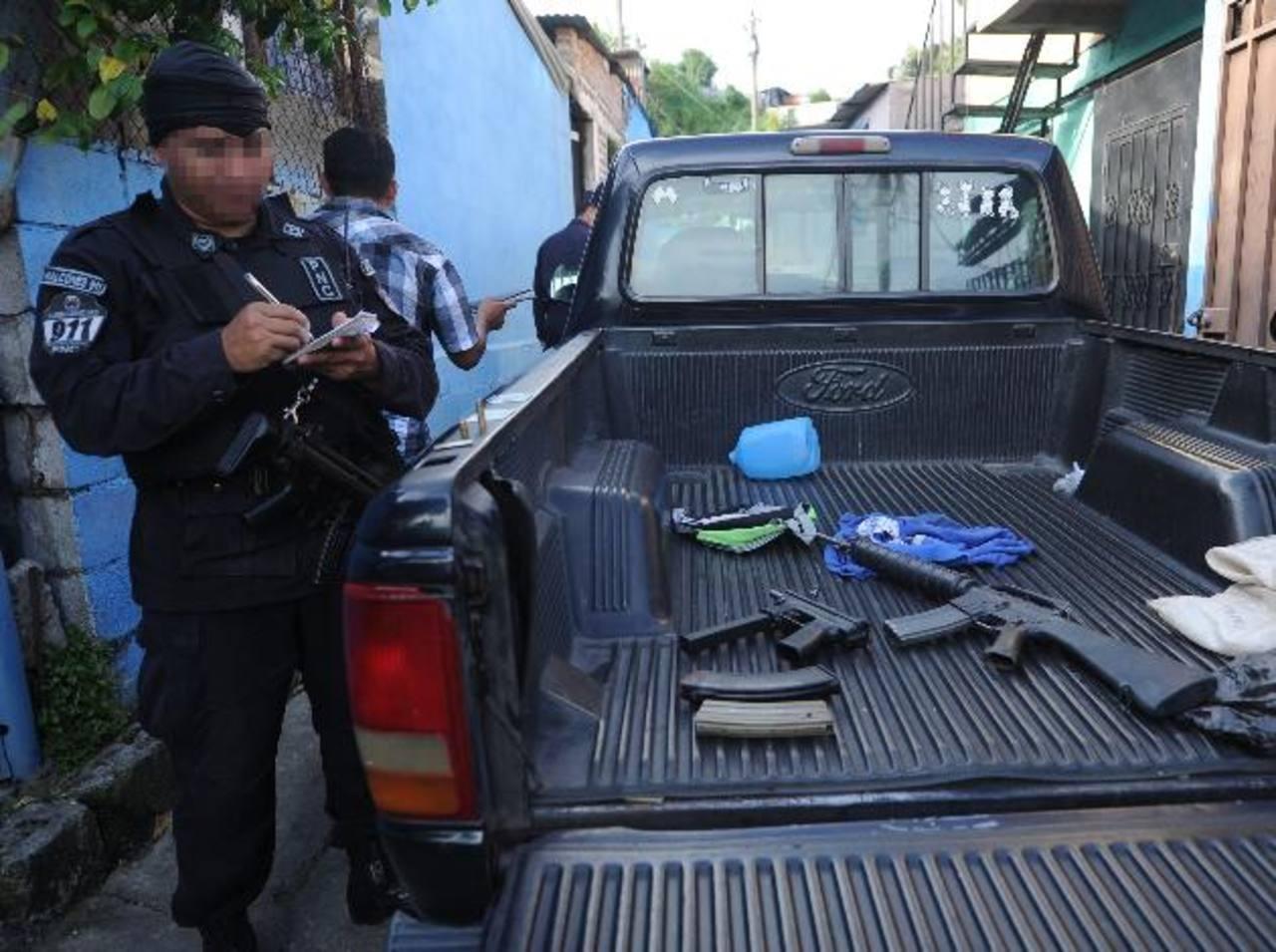 Un policía custodia un fusil y una subametralladora incautadas a pandilleros. Foto EDH / M. Hernández