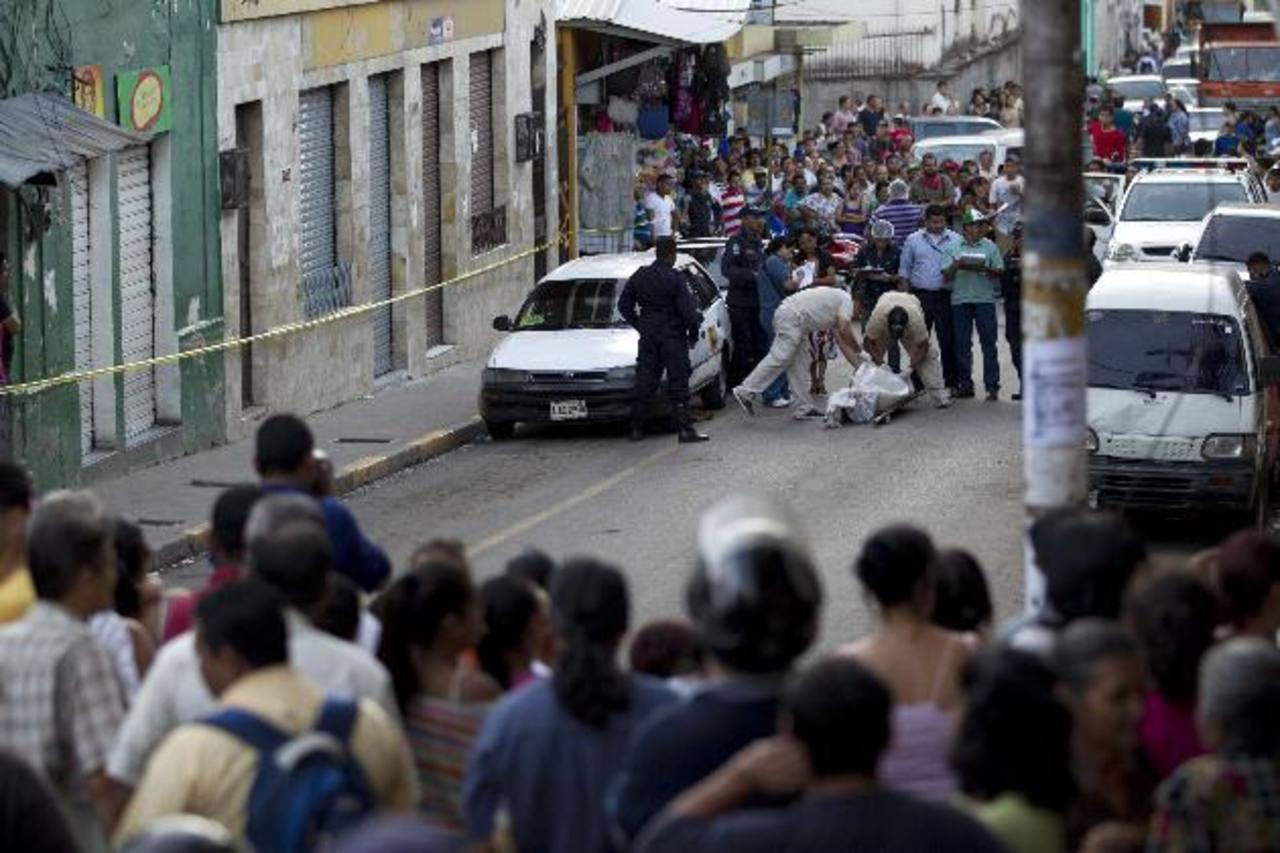 Un taxista fue asesinado el martes en Tegucigalpa, Honduras. La gente observa el trabajo de los forenses que retiran el cadáver del conductor. Foto EDH / AP