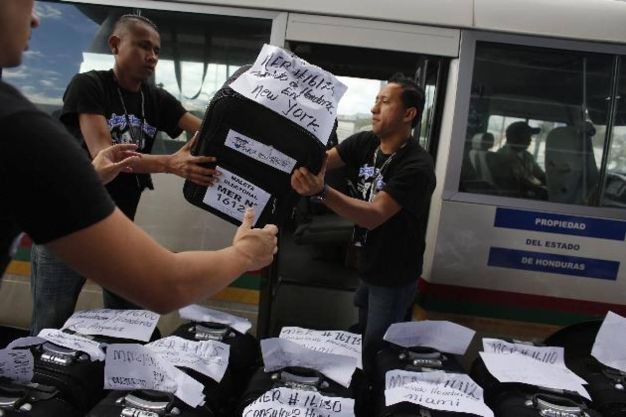 Miembros del Tribunal Electoral descargan en el aeropuerto Toncontín en Tegucigalpa, bolsas con material electoral para su distribución en los consulados de Honduras en los EE.UU. Foto/ Reuters
