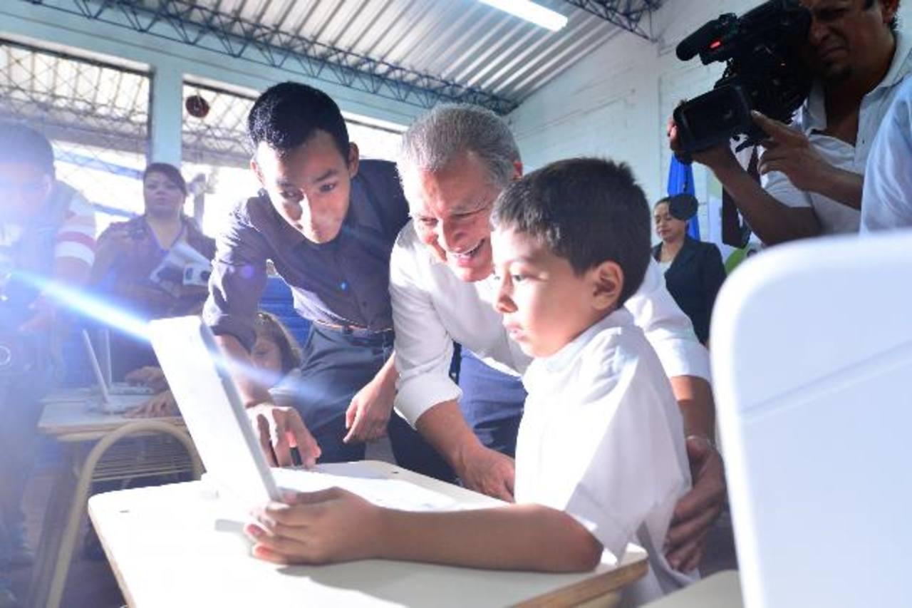 El candidato Salvador Sánchez Cerén observa jugar con una computador a un alumno de segundo grado de la escuela de la colonia Los Naranjos, de Apopa. foto edh / Omar Carbonero