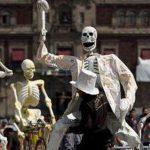 Un hombre transporta la representación de un esqueleto en preparación para una ofrenda por el Día de Muertos en el Zócalo de la Ciudad de México. Foto/ AP