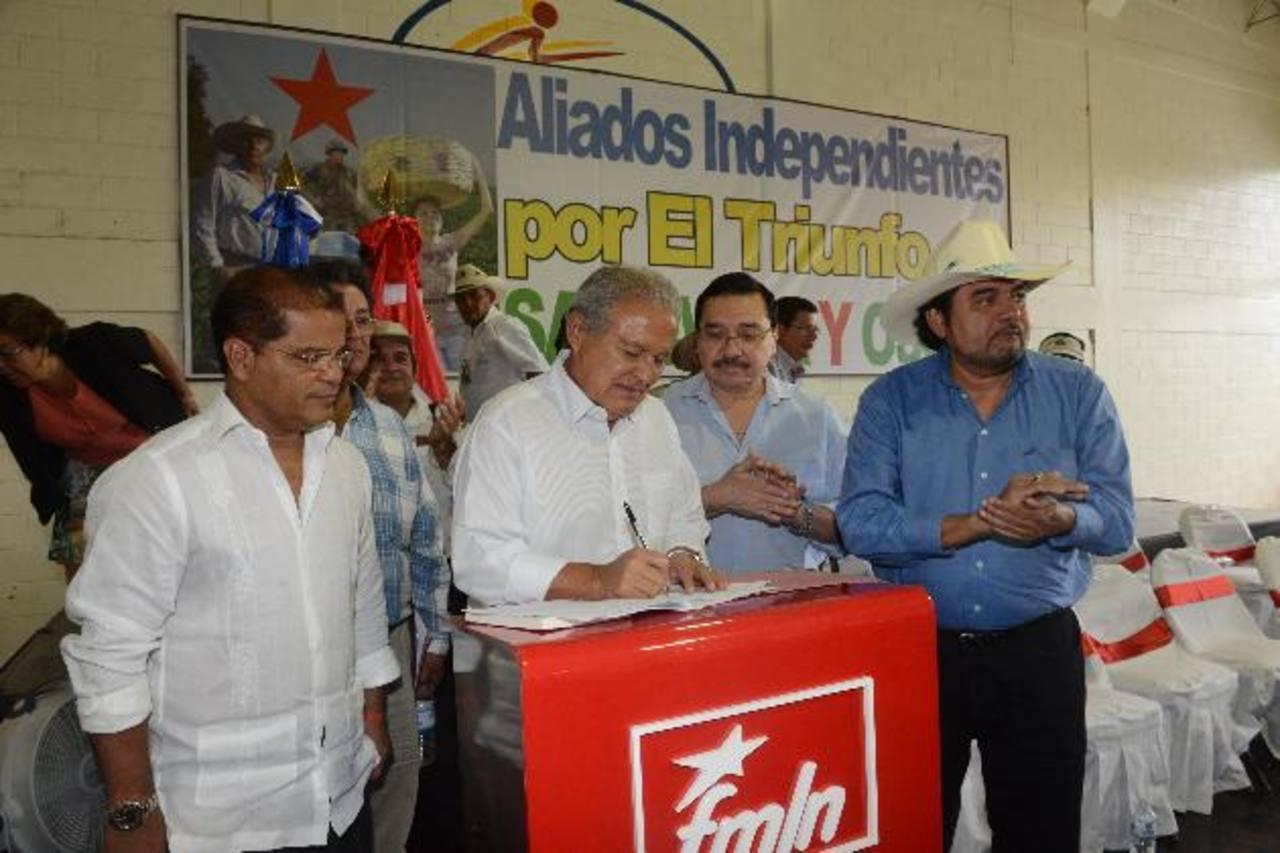Salvador Sánchez Cerén firma el compromiso de apoyar las propuestas hechas por Orlando Arévalo (derecha). Observa Óscar Ortiz y Medardo González. foto edh / Miguel Villalta