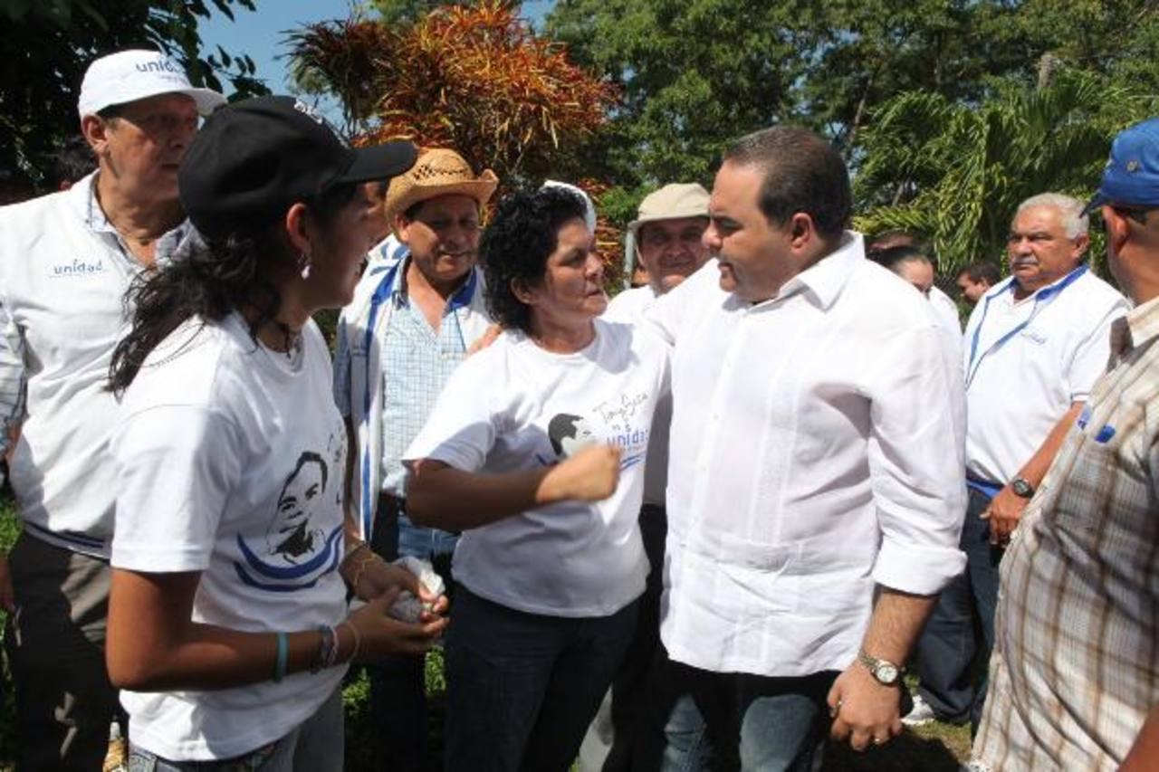 El candidato de Unidad, Tony Saca, (derecha), conversa con una simpatizante.