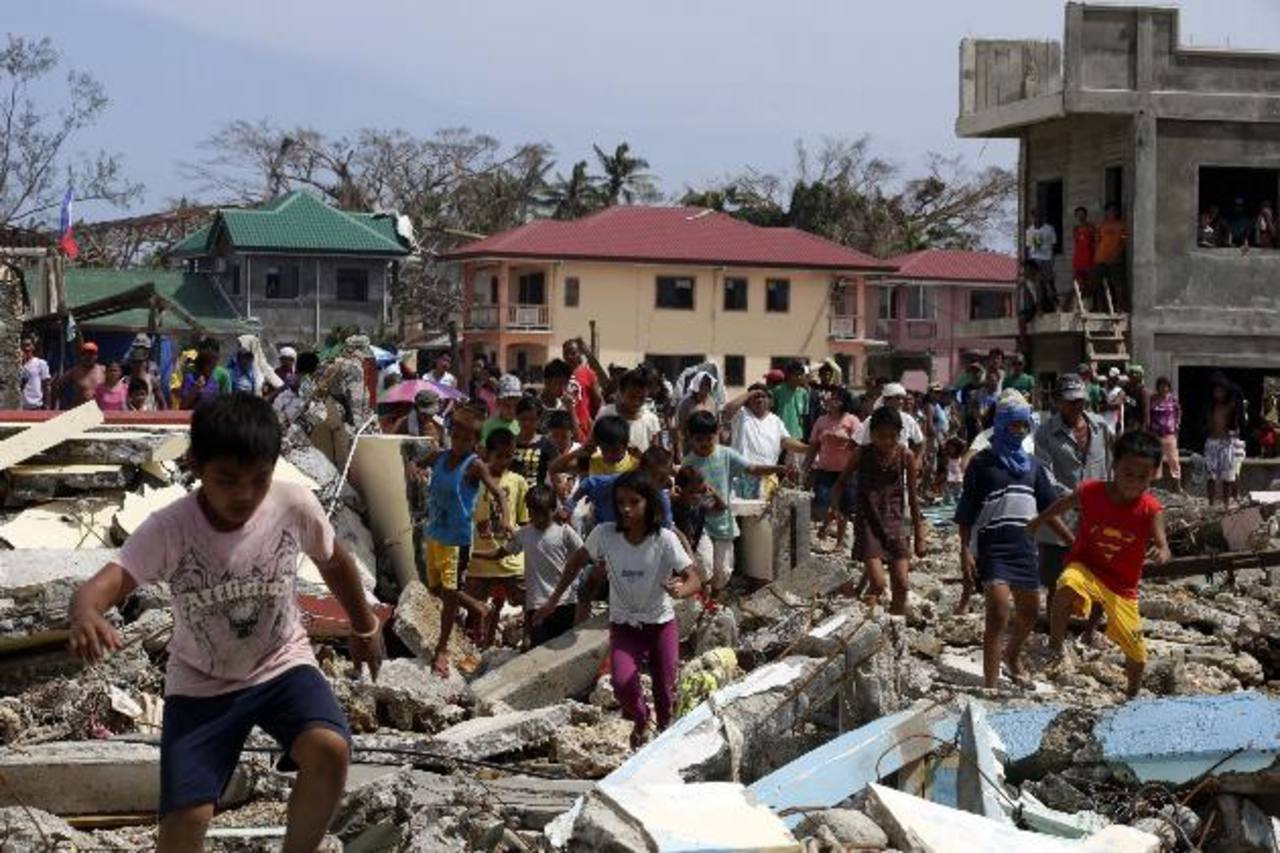 Decenas de filipinos corren entre los escombros en busca de ayuda humanitaria en las calles de la localidad de Guiuan, en la provincia de Leyte. foto edh / efe