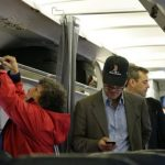 un pasajero con su teléfono celular en un avión en Boston.