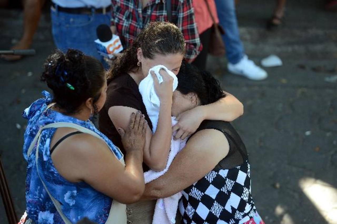 Parientes de Henry Alexander Montes, de 19 años, lloran frente a su cuerpo, que quedó tendido con varios balazos, en el área de venta de mariscos de La Tiendona. Foto EDH / Óscar Mira