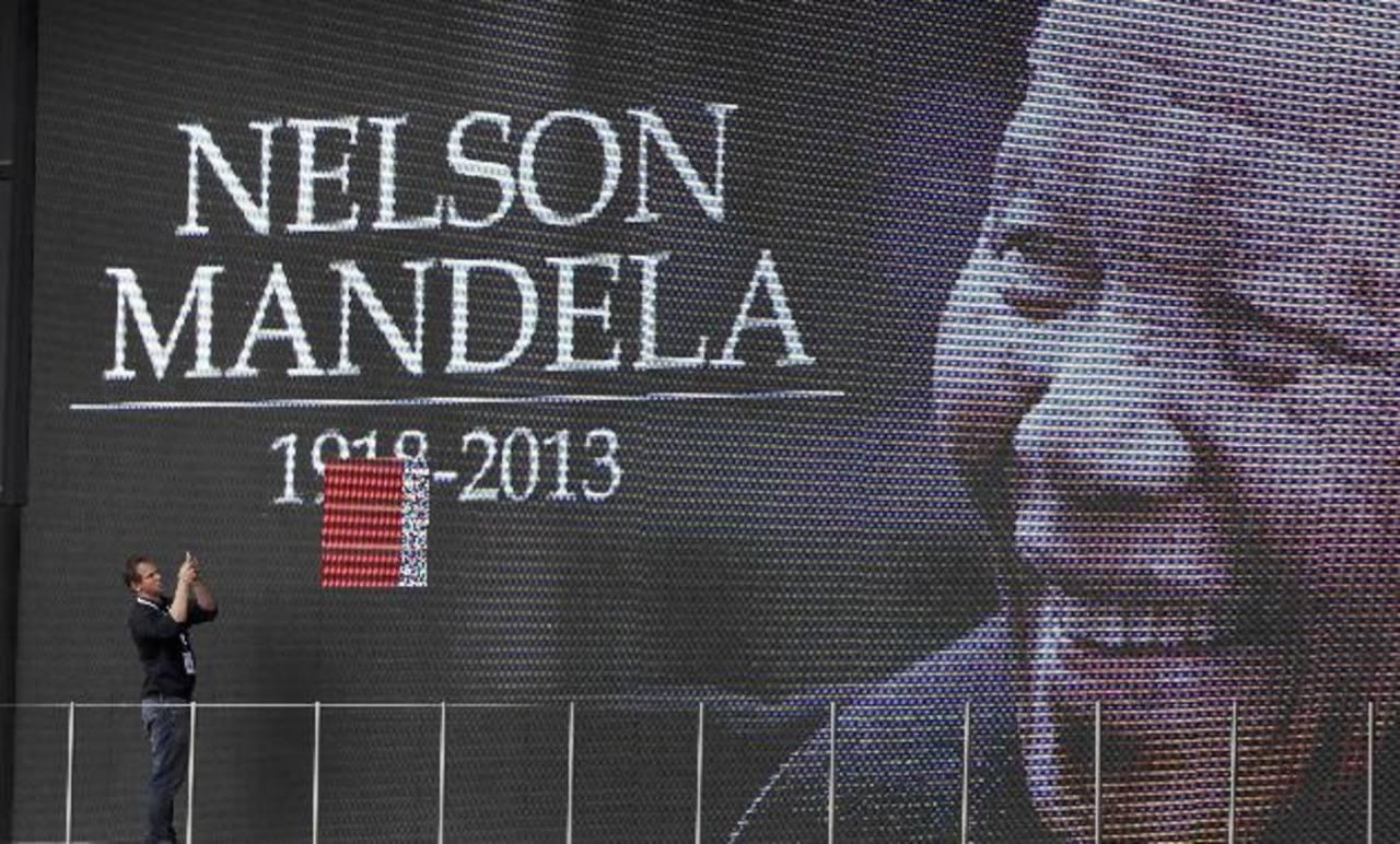 El rostro siempre sonriente de Mandela fue inmortalizado en este cartel gigante, colocado en el estadio de fútbol con ocasión de los servicios fúnebres del exmandatario. foto edh / AP