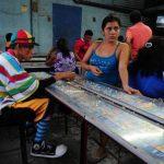 Leonel Alemán, quien se transforma en el Payaso K-Chinfly, se toma un receso en su jornada laboral y comparte algunos cartones de juego con su compañera Rocío Guerra. Después de vender toda la mañana en el mercado, Alicia Vásquez, de 63 años, acude a