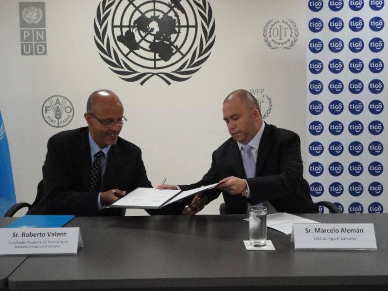 Robert Valent, representante residente de Naciones Unidas, firma convenio con Marcelo Alemán, gerente general de Tigo El Salvador. foto edh / cortesía