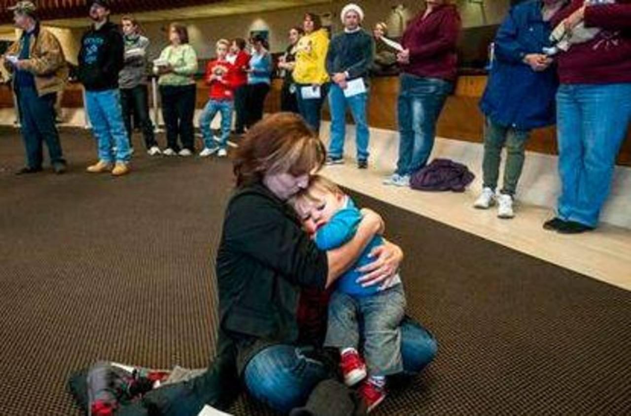 """Carla Coulter, de 36 años, abraza a su nieto mientras un coro local canta """"Noche de paz"""" en un foro en Flint, Michigan. Debido a una tormenta no hay luz, pero """"no necesito nada mas"""" que estar con la familia, dijo Coulter. Foto/ AP"""