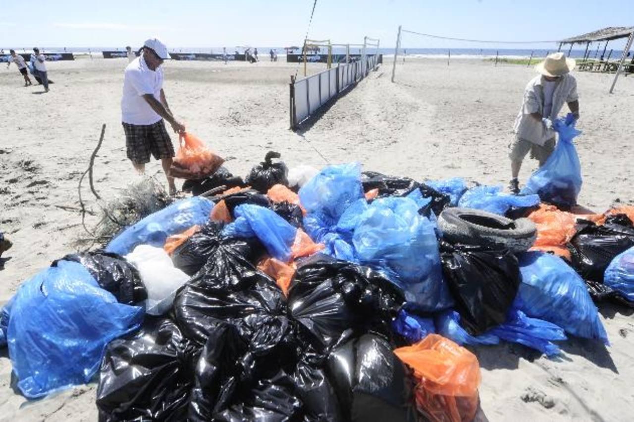 Bajo los intensos rayos del sol y el calor, los voluntarios trabajaron en equipo para quitar la basura . Fotos EDH / jorge reyes