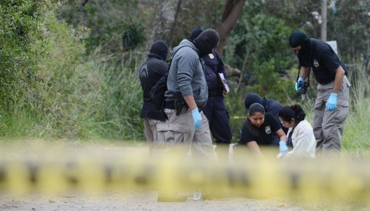 Investigadores de la Policía recogen evidencias del sitio donde hallaron el cadáver del empresario. Foto EDH / Claudia Castillo