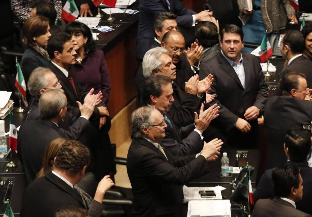 Diputados del PRI aplauden después de aprobar la reforma energética en el Senado. foto edh / reuters