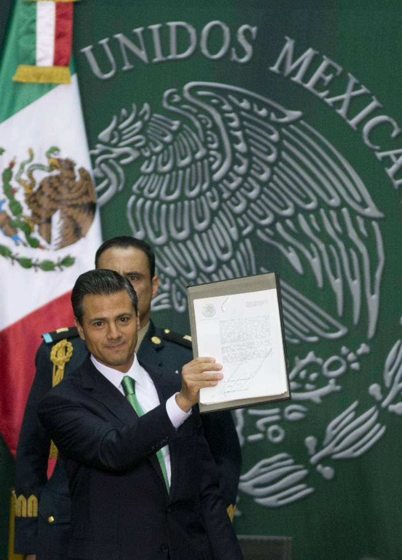 Peña Nieto sostiene el documento firmado que contiene la reforma. foto edh / AP