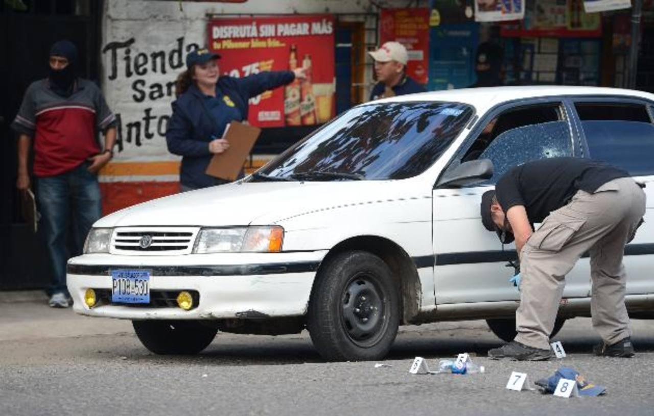 Investigadores policiales y fiscales recaban evidencias donde fue asesinado el agente José Nazario Pérez, quien viajaba con cuatro familiares en el carro blanco. La víctima mató a dos asaltantes al tratar de defenderse. Foto EDH / Mauricio Cáceres
