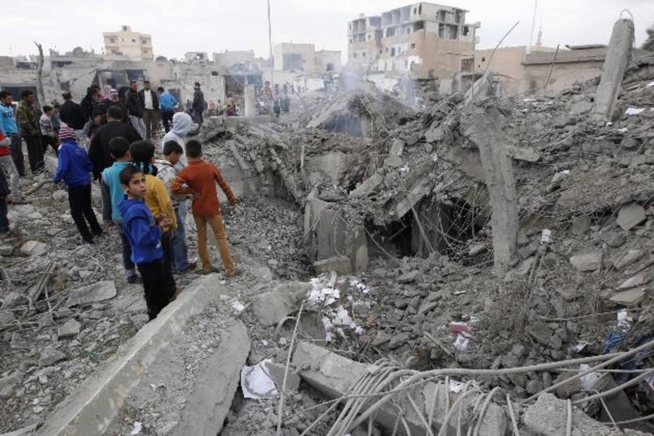Sirios inspeccionan edificio que habría sido dañado por un misil Scud de las fuerzas leales al presidente de Siria. foto / reuters