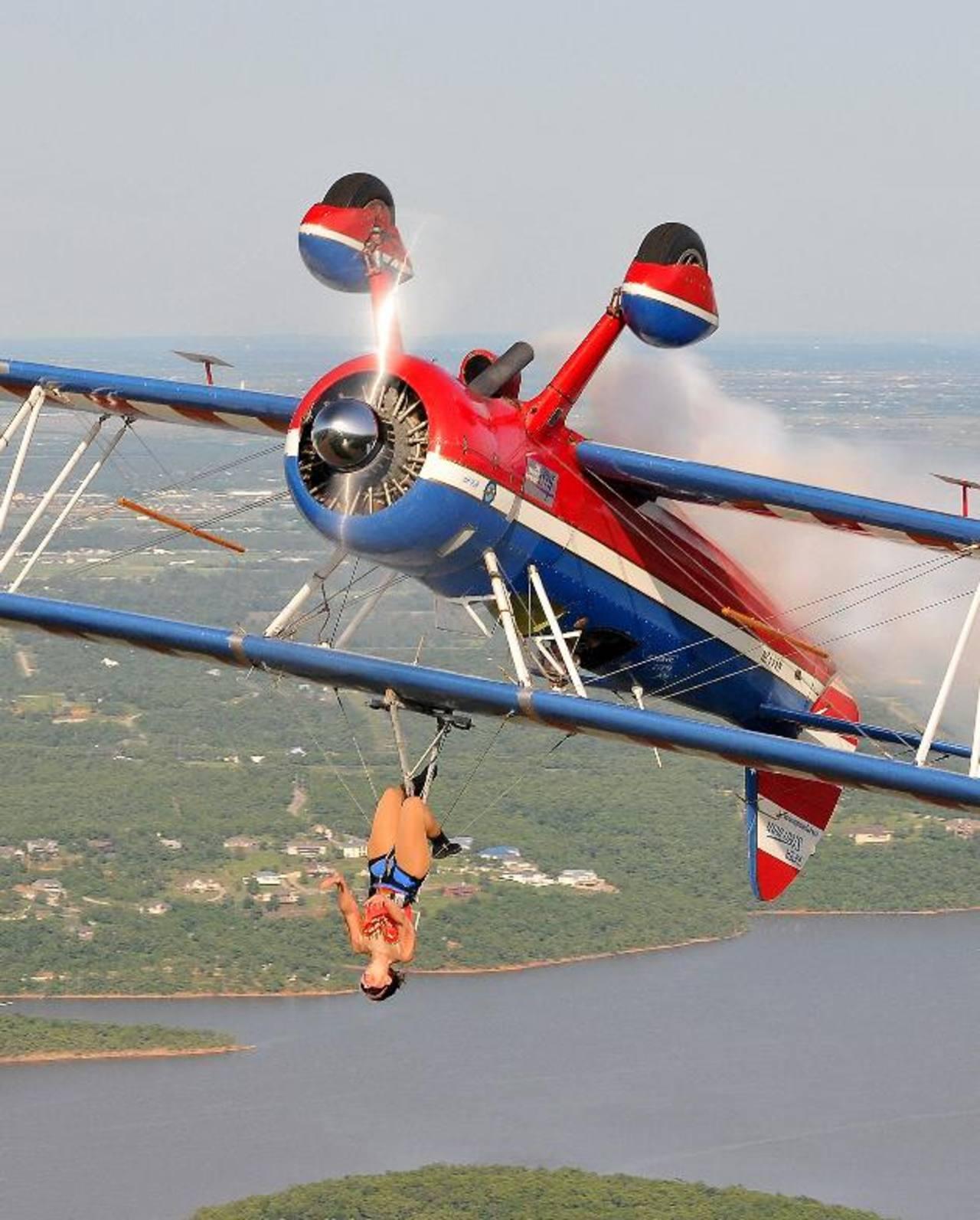 Ashley Battles y el piloto Greg Shelton realizan atrevidas piruetas en leno vuelo. Ella no usa paracaídas.
