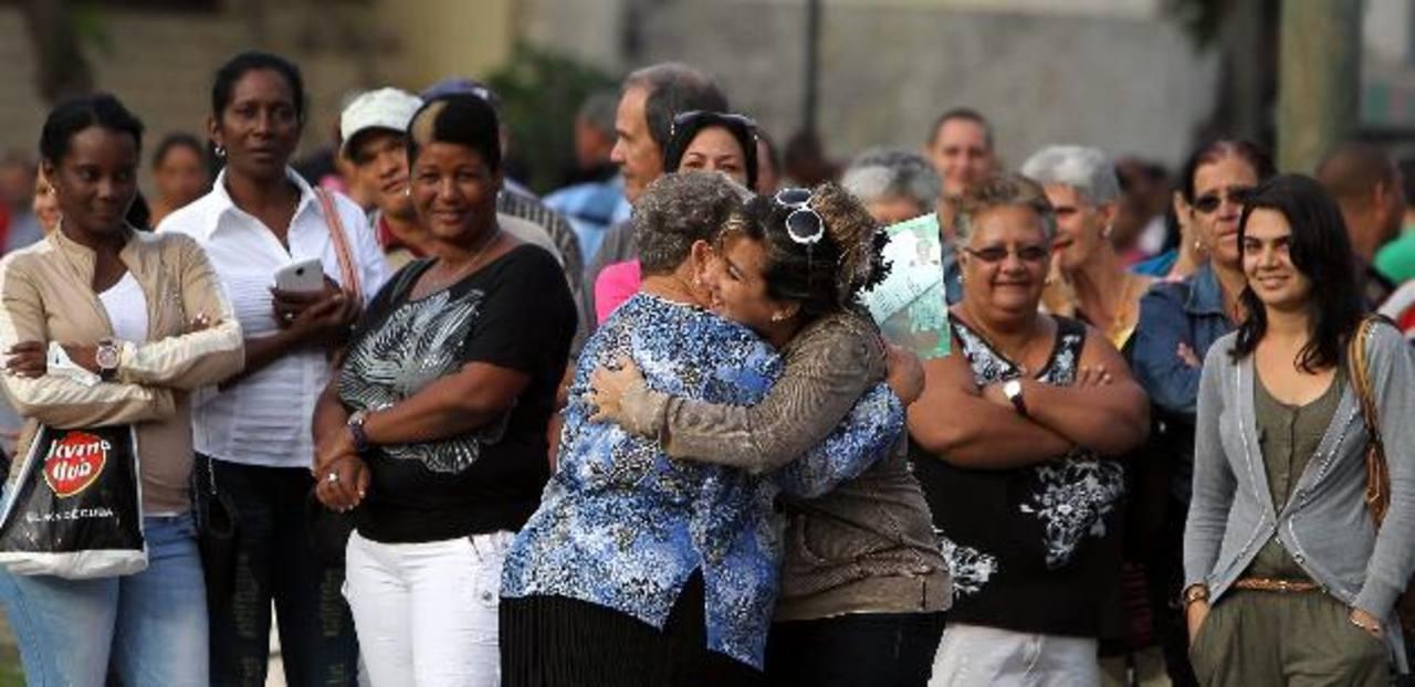 Dos mujeres se abrazan luego de que una de ellas obtuviera un visado en la Sección de Intereses de EE. UU. (SINA), en La Habana, Cuba. foto edh /efe