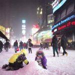 Dos niños disfrutan de la nieve en plena calle en el área de Times Square, durante la tormenta de nieve, el jueves 2 de enero del 2014, en Nueva York