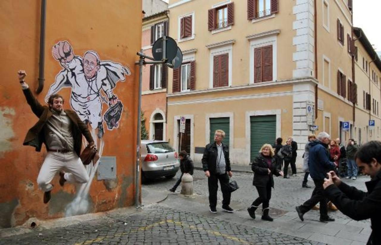 """Muchas personas se detienen para posar junto al grafiti del """"Superpapa"""". Foto/ AP"""