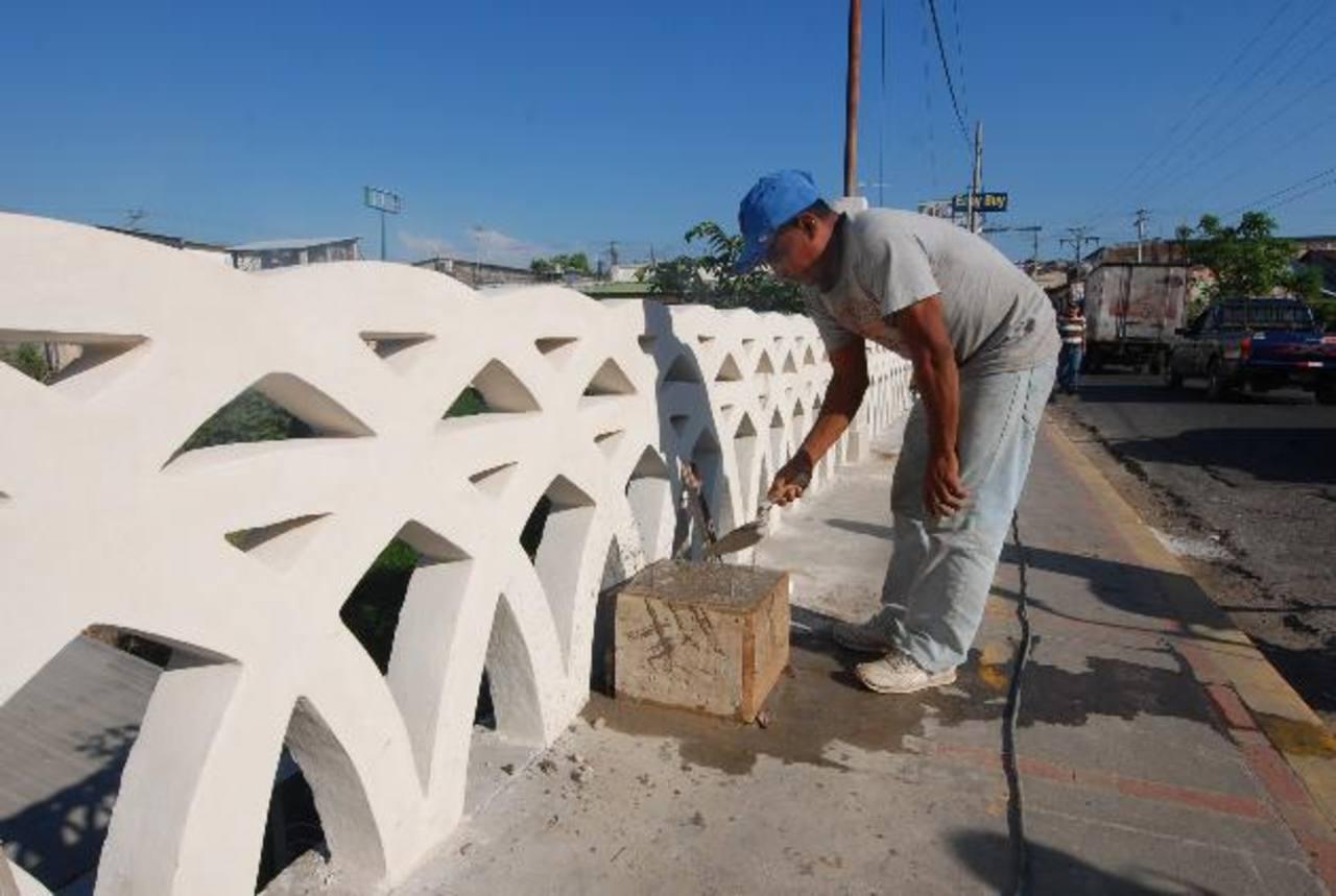 Empleados municipales realizan los últimos detalles en el puente. foto edh / cristian díaz