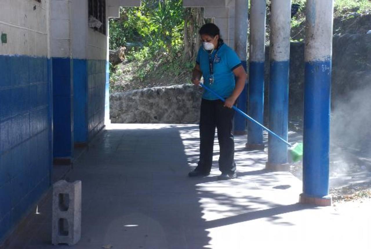 En el Instituto Federico García Prieto, del cantón Conacastal, el personal se protege como puede al limpiar. Fotos EDH / Carlos Segovia
