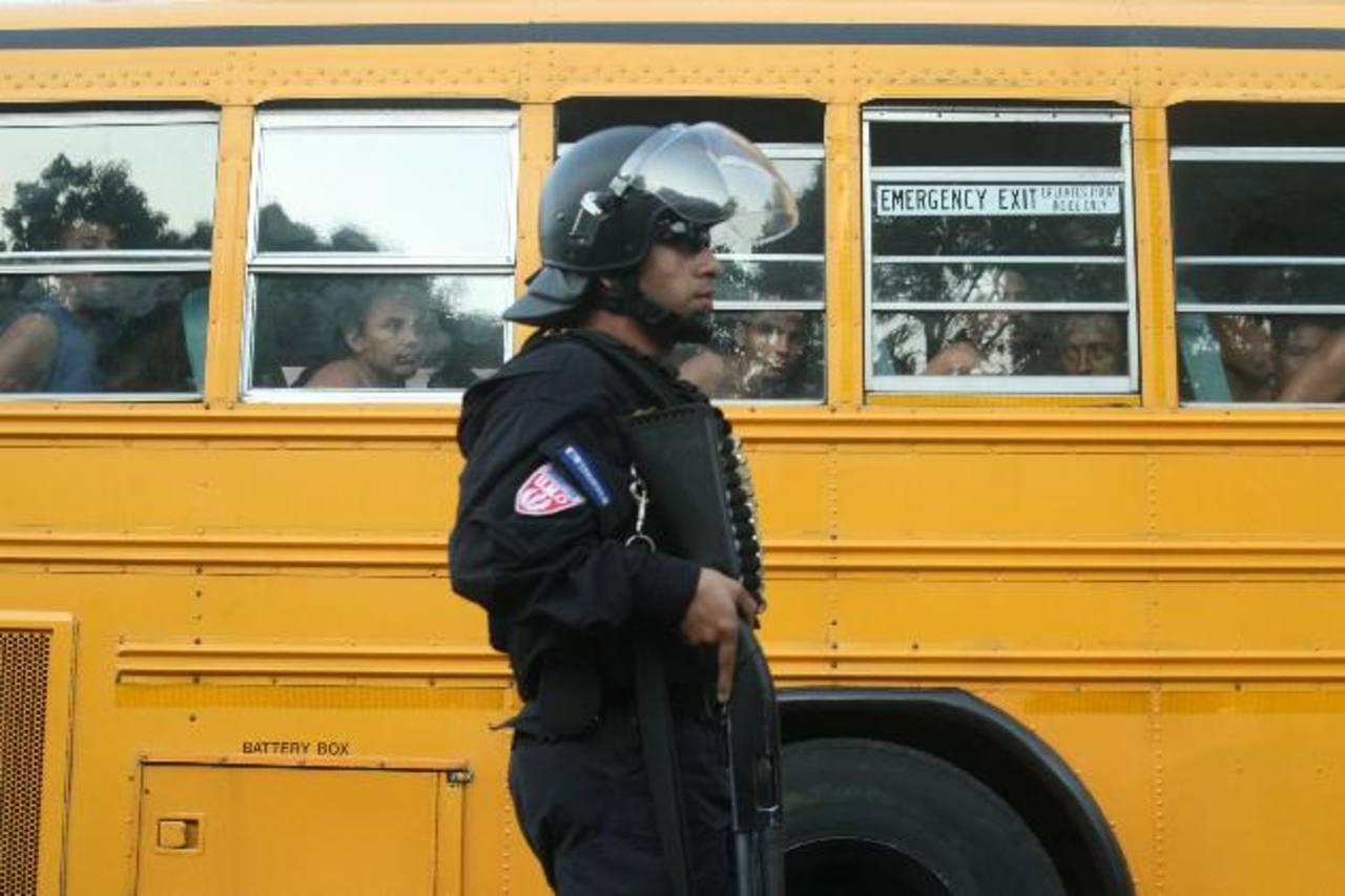 Un agente antimotín custodia un autobús donde son trasladados reos desde el penal de Mariona hacia otros reclusorios.