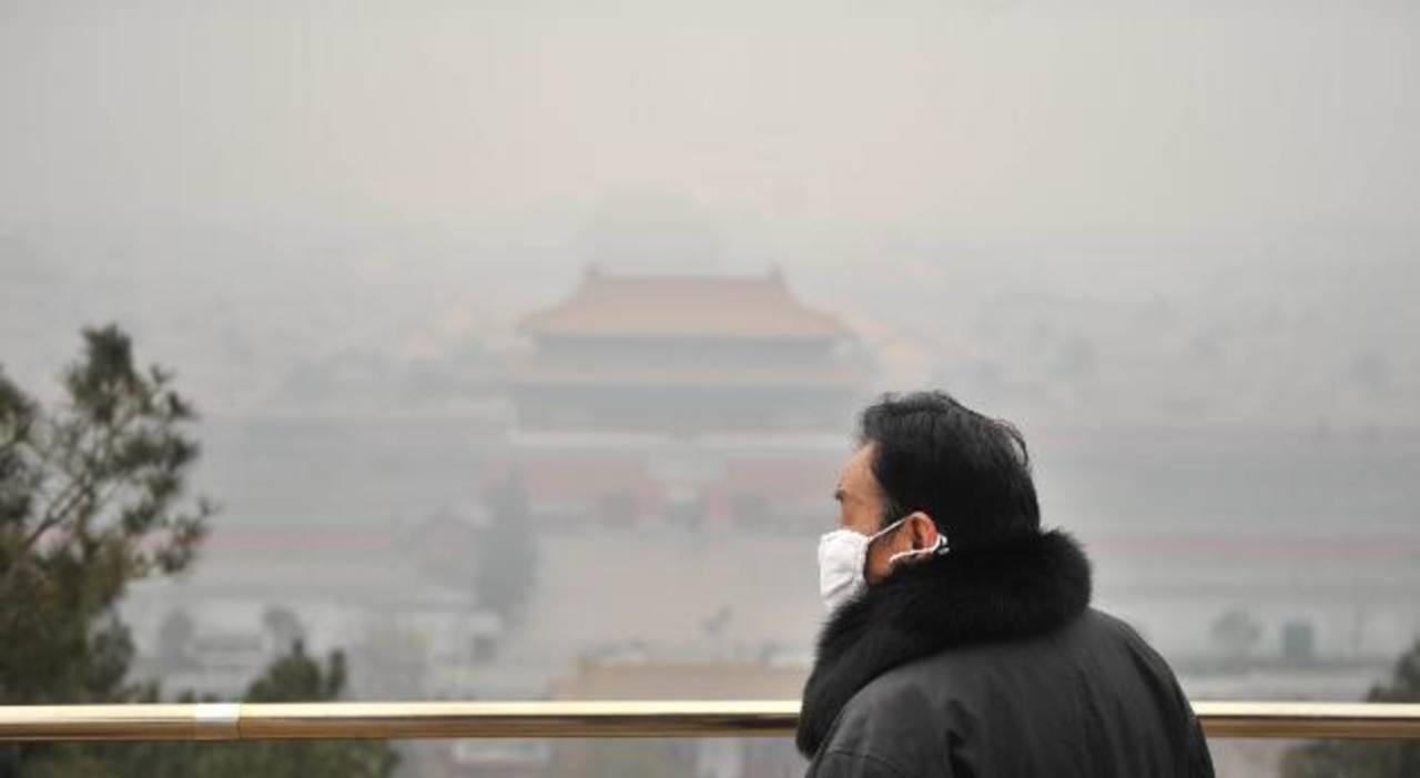Un turista utiliza una mascarilla mientras observa el Palacio Imperial