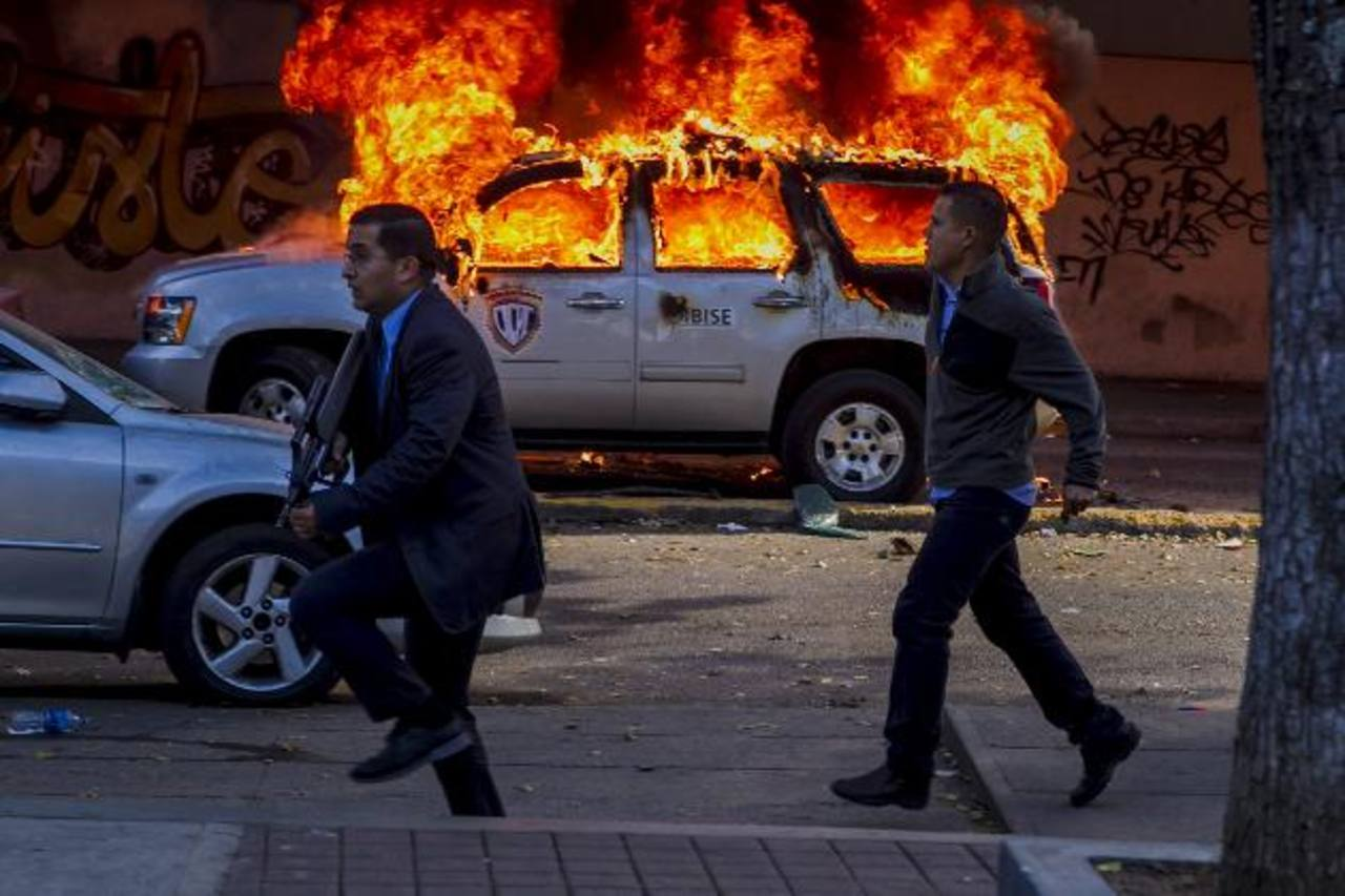 Miembros de la Policía Científica (CICPC) de Venezuela corren frente a un vehículo incendiado. foto edh / efe