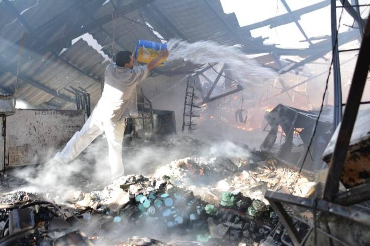 Bomberos y vendedores del centro de abastos trabajaron en sofocar el fuego en una comercial migueleña. foto edh / carlos segovia