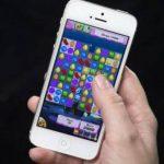 Una mujer posa para una ilustración fotográfica donde exhibe el juego Candy Crush en un teléfono iPhone. Foto/ Reuters