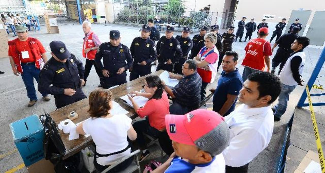 Varios agentes de la Policía Nacional Civil (PNC) hacen fila para emitir su voto en el colegio Sagrado Corazón, en San Salvador. Foto EDH / Mario Amaya