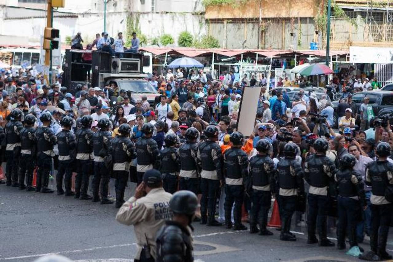 Un cordón policial bloquea el paso de los periodistas a la sede de la institución que autoriza las divisas en Venezuela. foto edh / EFE