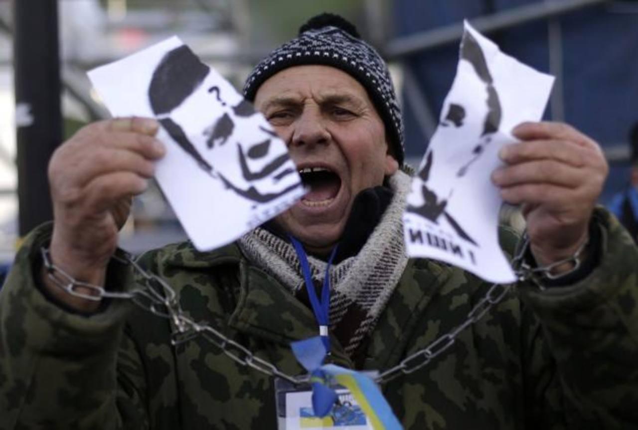 Un manifestante rompe el retrato del dictador Víktor Yanukóvich.