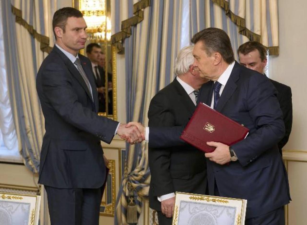 El presidente de Ucrania Viktor Yanukovich estrecha la mano del opositor