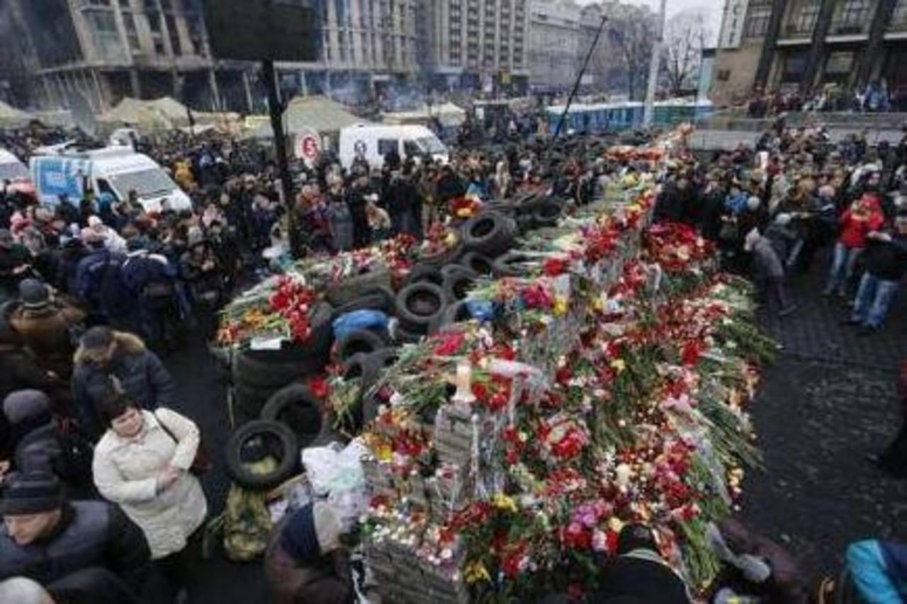 La gente rodea un improvisado memorial mientras se reúne para recordar a las víctimas de los recientes enfrentamientos en el centro de Kiev. Foto/ Reuters