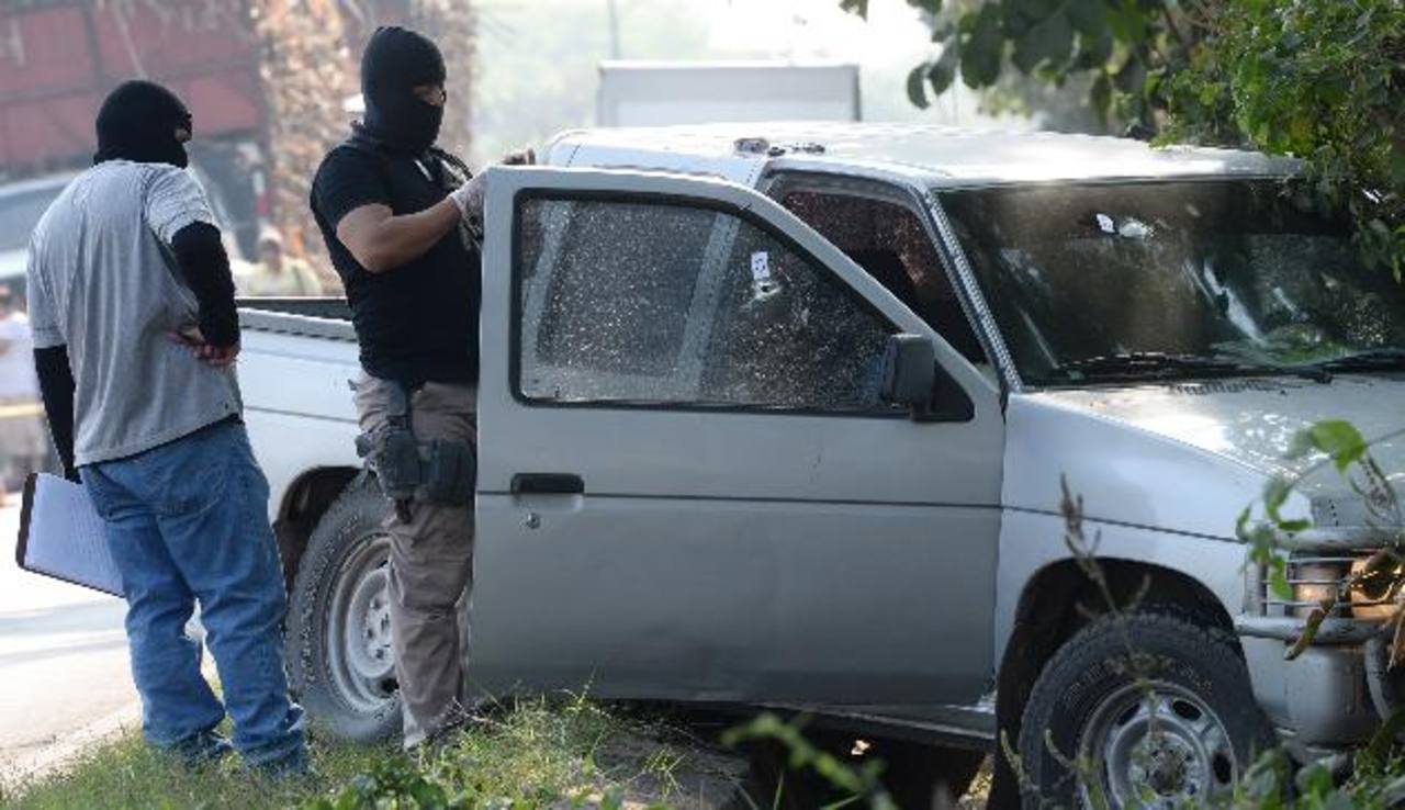 Investigador inspecciona el pick up que conducía el cooperativista Máximo Antonio Orellana Hernández, asesinado ayer en el desvío al ingenio La Cabaña. Foto EDH / Claudia Castillo.