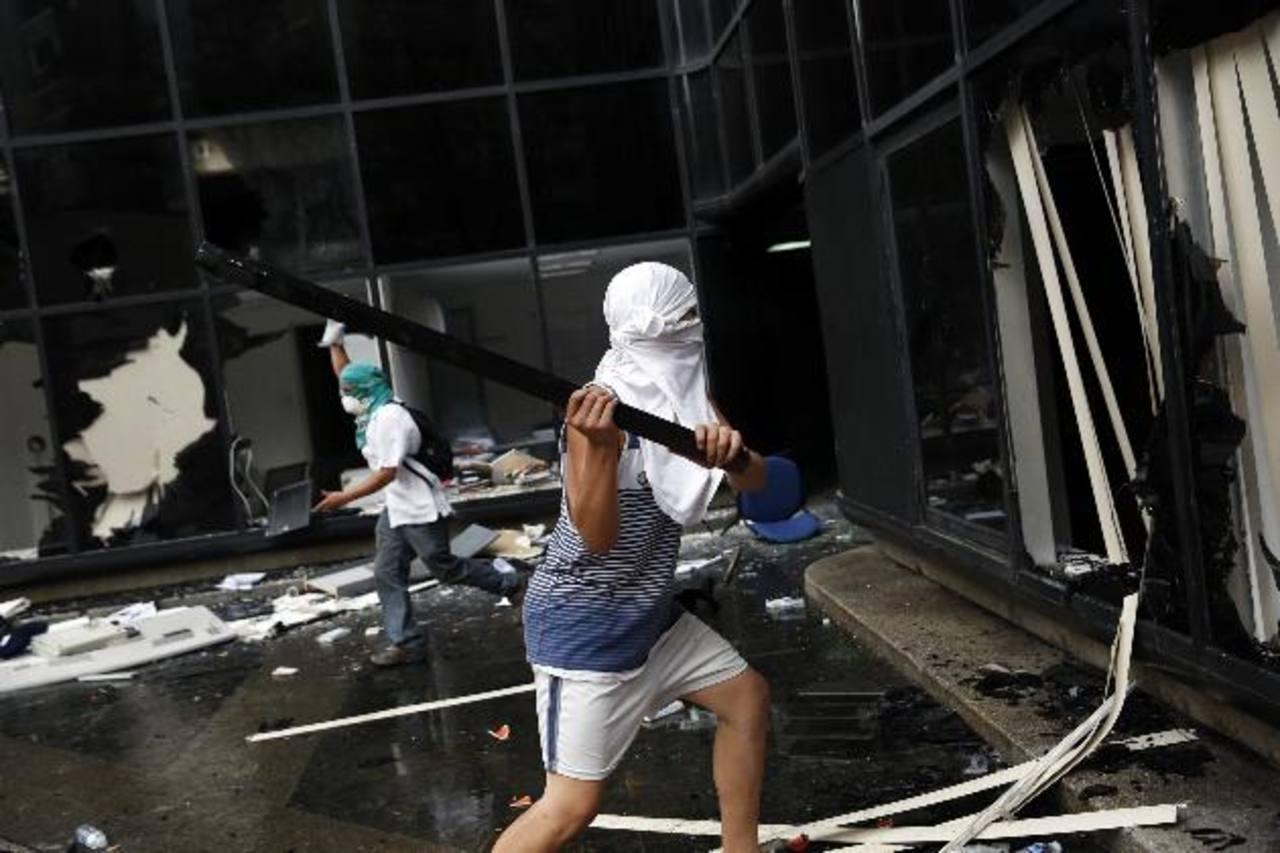 Un manifestante protesta contra las medidas económicas destruyendo los ventanales de un edificio público. La falta de productos en Venezuela presionó además la inflación, que se disparó hasta un 56 por ciento anual.