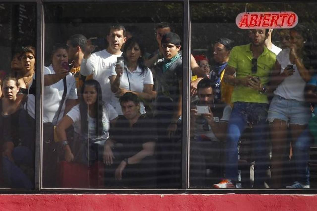Clientes de un restaurante en Caracas observan las protestas callejeras contra el gobierno de Nicolás Maduro.